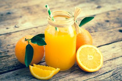 Apfelsinen mit Blättern, Schnitze und Apfelsinensaft auf einem Holzbrett